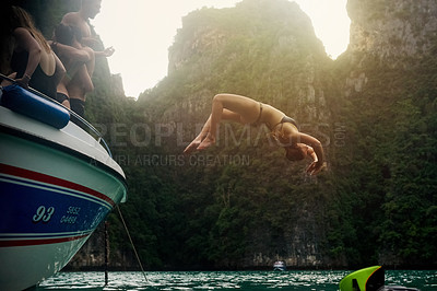Buy stock photo Shot of a young woman doing a backflip off a boat while her friends watch