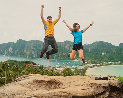 Buy stock photo Shot of a happy young couple jumping in front of an island landscape