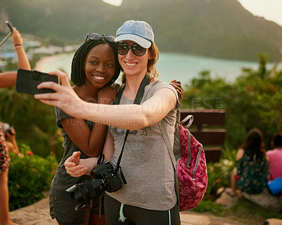 Buy stock photo Portrait of two happy friends taking a selfie on an island vacation