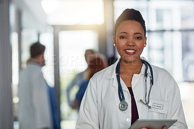 Buy stock photo Portrait of a young female doctor standing in a hospital with her colleagues in the background