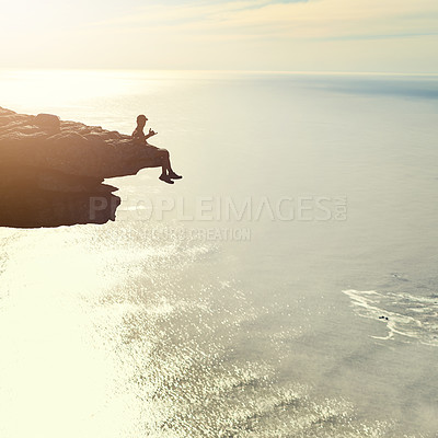 Buy stock photo Shot of an unidentifiable young man admiring an ocean view from a mountain overhang