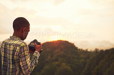 Buy stock photo Cropped shot of a young man taking photos of a scenic view