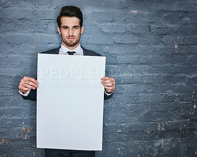 Buy stock photo Shot of a businessman holding up a blank placard