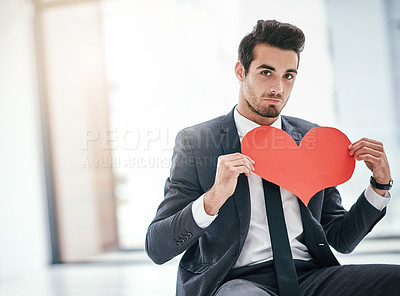 Buy stock photo Portrait of a trendy young businessman posing with a paper heart in the office
