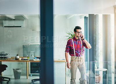 Buy stock photo Cropped shot of a handsome young designer talking on his cellphone in the office
