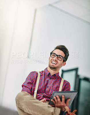 Buy stock photo Cropped shot of a handsome young designer using a digital tablet in his office