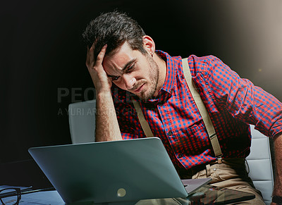 Buy stock photo Shot of a frustrated young designer looking stressed while working on his laptop