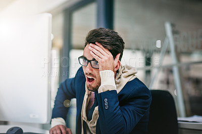Buy stock photo Shot of a trendy young businessman looking surprised while using his computer in the office