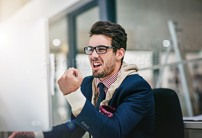 Buy stock photo Shot of a trendy young businessman celebrating good news at his computer