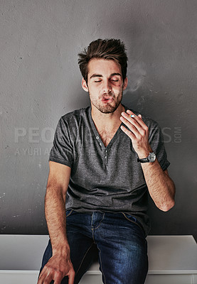 Buy stock photo Cropped shot of a beaten and bruised young man smoking a cigarette