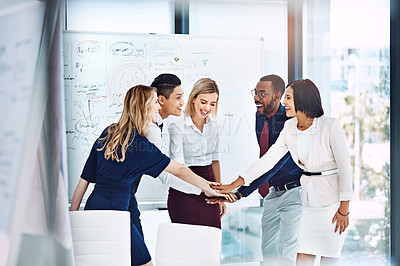 Buy stock photo Shot of a group of businesspeople standing with their hands in a huddle  in the office