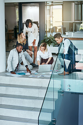 Buy stock photo Shot of a group of coworkers working together while gathered on the floor