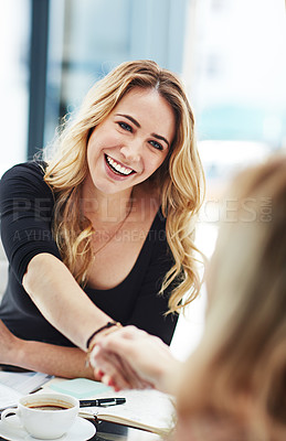 Buy stock photo Shot of two colleagues shaking hands during a meeting at work