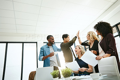 Buy stock photo Shot of colleagues celebrating with a high five during a brainstorming session at work