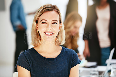 Buy stock photo Portrait of an ambitious young woman in a modern office with her colleagues in the background