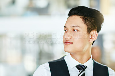 Buy stock photo Shot of a confident young businessman working in a modern office