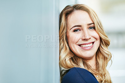 Buy stock photo Portrait of a confident young businesswoman leaning against a wall in an office