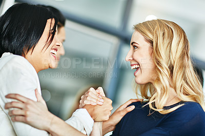 Buy stock photo Shot of two businesswomen gripping hands in solidarity at work