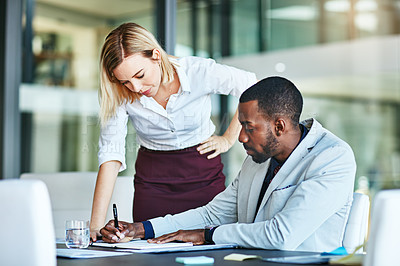 Buy stock photo Shot of two colleagues having a meeting in a modern office