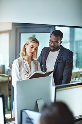 Buy stock photo Shot of two colleagues using a notebook together at work