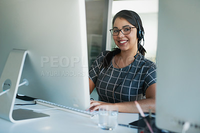 Buy stock photo Portrait of a young woman wearing a headset and using a computer at her work desk