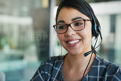 Buy stock photo Shot of a happy young woman using a headset at work