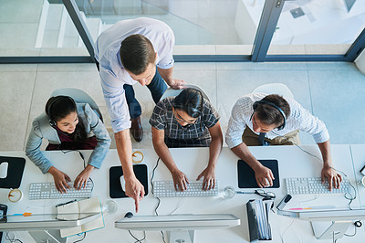 Buy stock photo High angle shot of a man assisting his colleagues in a call center