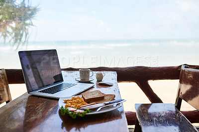 Buy stock photo Shot of a laptop and freshly made breakfast on a table with a view of the beach in the background
