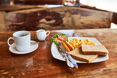 Buy stock photo Shot of a cup of coffee and freshly made breakfast on a table