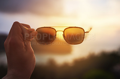 Buy stock photo Cropped shot of an unidentifiable tourist holding up a pair of sunglasses over a tropical view