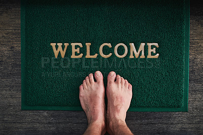 Buy stock photo High angle shot of a man's bare feet standing on a welcome mat