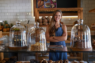 Buy stock photo Portrait of a young business owner standing behind the counter of her bakery