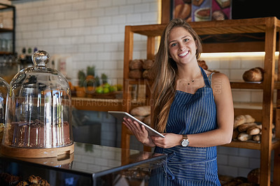 Buy stock photo Portrait of a young business owner using a digital tablet in her bakery