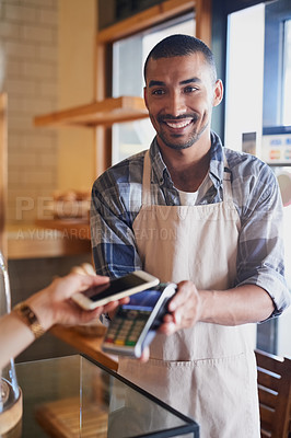 Buy stock photo Cropped shot of a waiter processing a payment from a customer using NFC technology