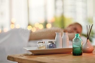 Buy stock photo Cropped shot of various pampering essentials in a spa with a young woman in the background