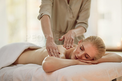 Buy stock photo Cropped shot of a young woman enjoying a back massage at a spa