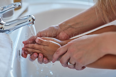 Buy stock photo Closeup shot of a mother helping her little girl wash her hands at the bathroom sink