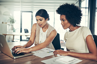 Buy stock photo Cropped shot of two colleagues working together on a laptop in an office