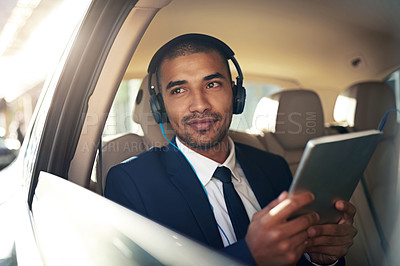 Buy stock photo Shot of a businessman listening to music on his tablet while sitting in his car