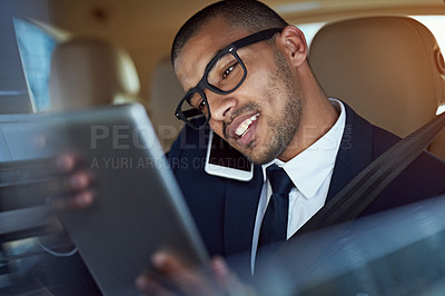 Buy stock photo Shot of a businessman talking on his phone while looking at his tablet in the back seat of a car