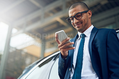 Buy stock photo Shot of a businessman using his phone while standing outside