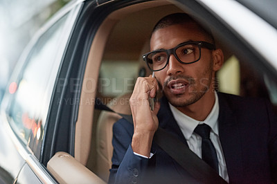 Buy stock photo Shot of a young businessman talking on his phone while sitting in his car