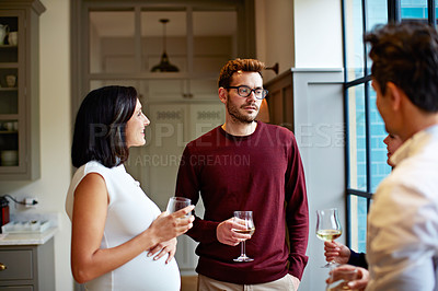 Buy stock photo Shot of a group of friends drinking wine and talking together in a kitchen at a get-together