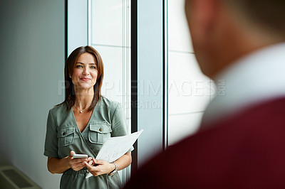 Buy stock photo Shot of two colleagues talking together in an office hallway