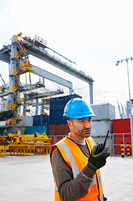 Buy stock photo Shot of a young man in workwear standing outside on a large commercial dock talking on a walkie-talkie