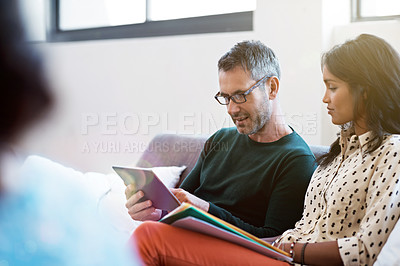 Buy stock photo Shot of a group of colleagues working together while sitting on a sofa in an office