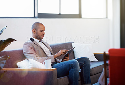 Buy stock photo Shot of a young man sitting on a sofa in an office using a digital tablet