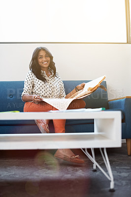Buy stock photo Portrait of a young woman sitting on a couch in an office reading a newspaper