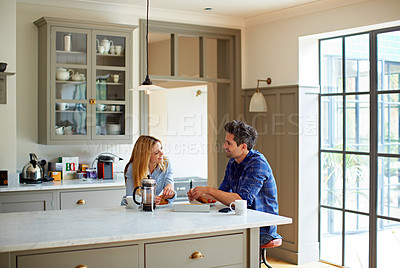 Buy stock photo Shot of a young couple having breakfast in their kitchen