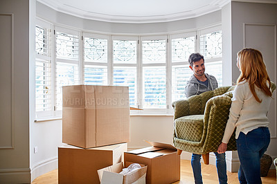 Buy stock photo Shot of a happy young couple carrying a chair in their new house